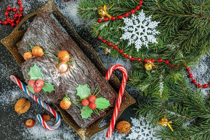 Stock image of 'Traditional Christmas Cake log, candy, tree branches and garland on a snowy wooden background. '