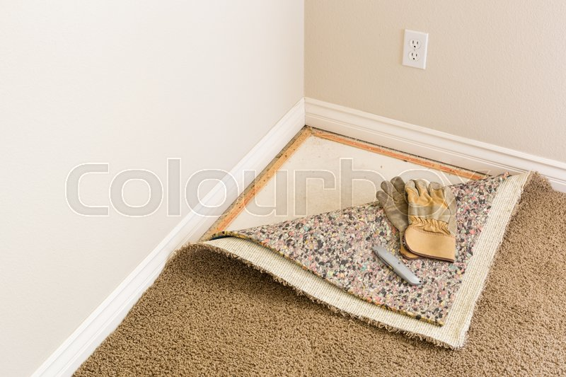 Stock image of 'Construction Gloves and Utility Knife On Pulled Back Carpet and Pad In Room.'