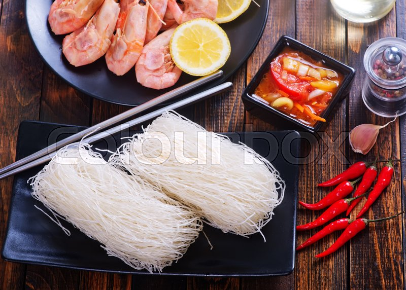 Stock image of 'rice noodles on plate and on a table'
