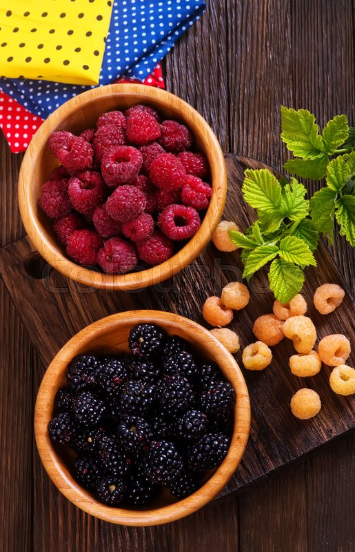 Stock image of 'fresh berries in bowl and on a table'