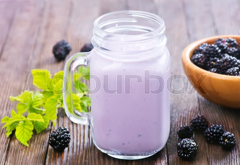 Stock image of 'blackberry yogurt in glass and on a table'