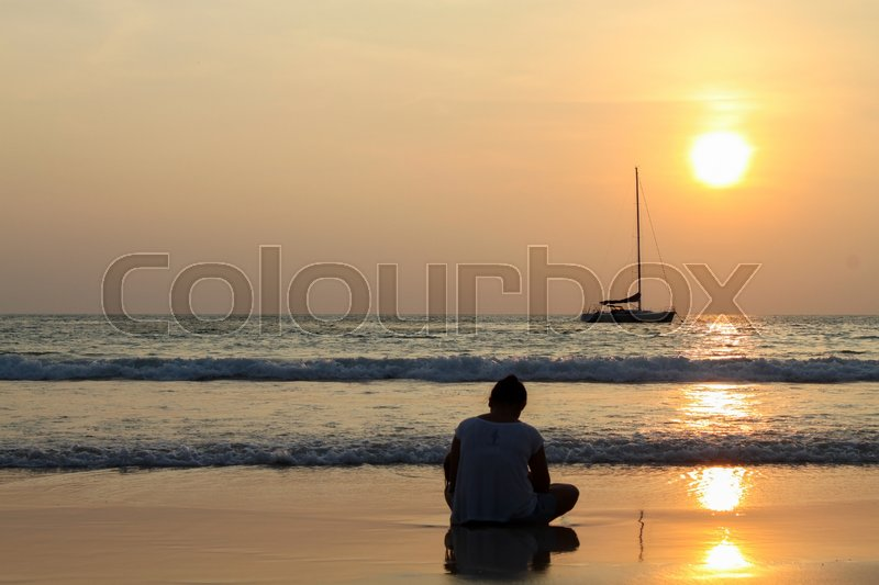 Stock image of 'A girl sitting by the sea at sunset and looking at a passing boat, in a light summer dress. She looks at the sea. Sun sets over the horizon.'