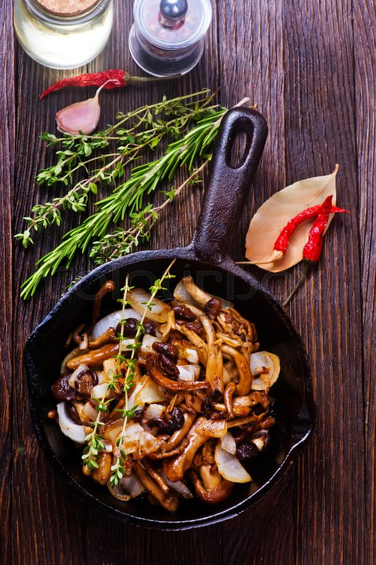 Stock image of 'fried mushroom in pan and on a table'
