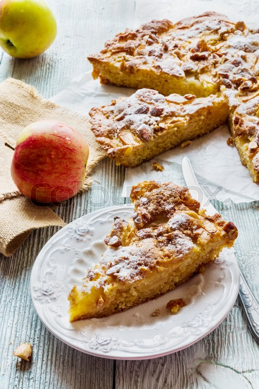 Homemade apple and almond cake. Piece of pie on white plate and fresh fruits on wooden background, stock photo