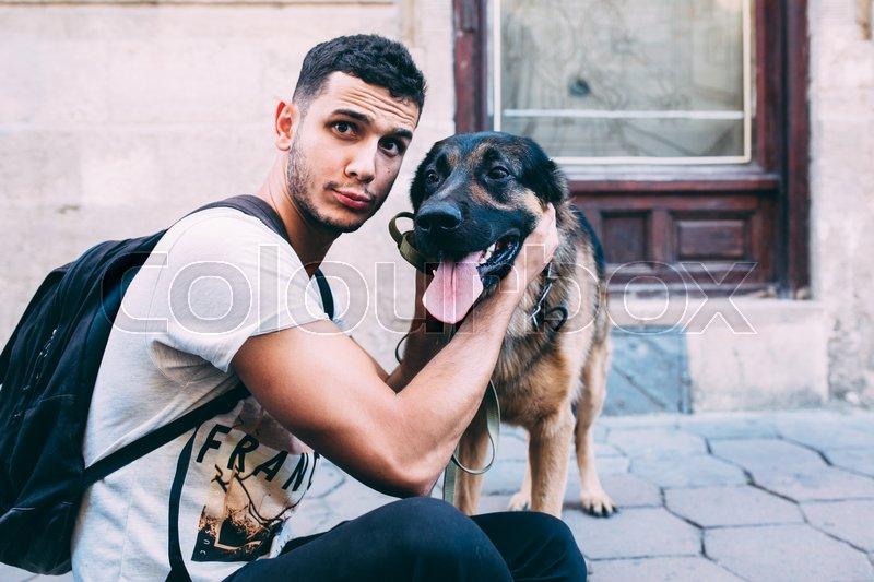 Man and dog on the sidewalk posing on camera, stock photo