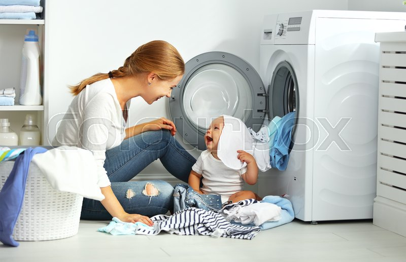 Mother a housewife with a baby engaged in laundry fold clothes into the washing machine, stock photo