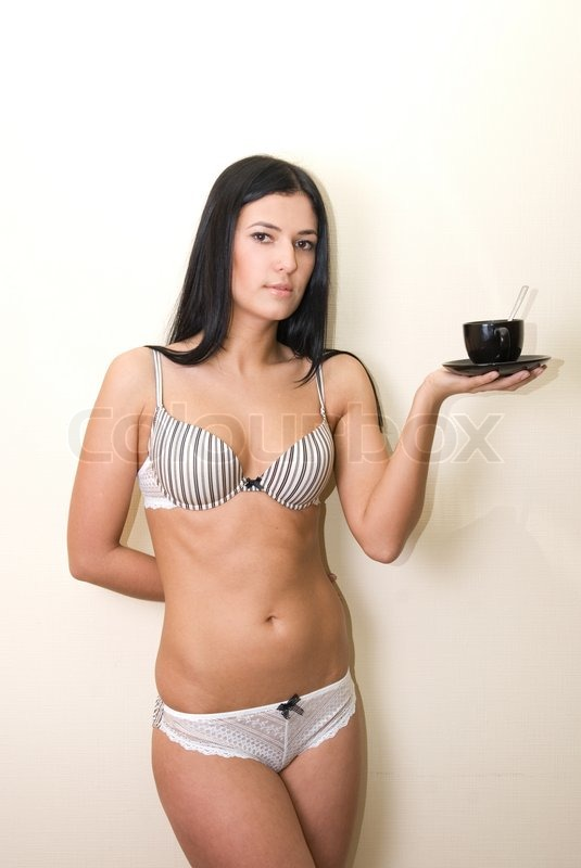 Stock image of 'Sexy girl in lingerie at wall background with coffee cup'