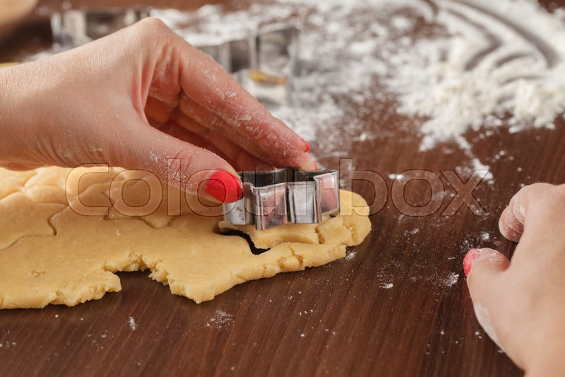 Hand Cutting Out Shapes from Rolled Out Ginger Cookies Dough with Star Cutters, stock photo