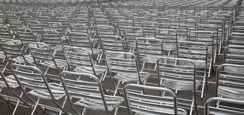 rows of empty metal chairs after rain at an outdoor urban arena at summertime