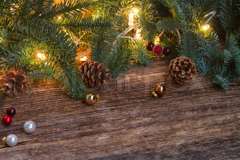 Christmas border with fir tree and glowing lights on old wooden background, stock photo