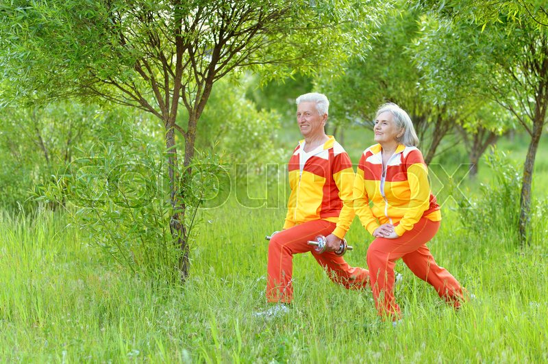 Stock image of 'Happy fit senior couple exercising in  park'