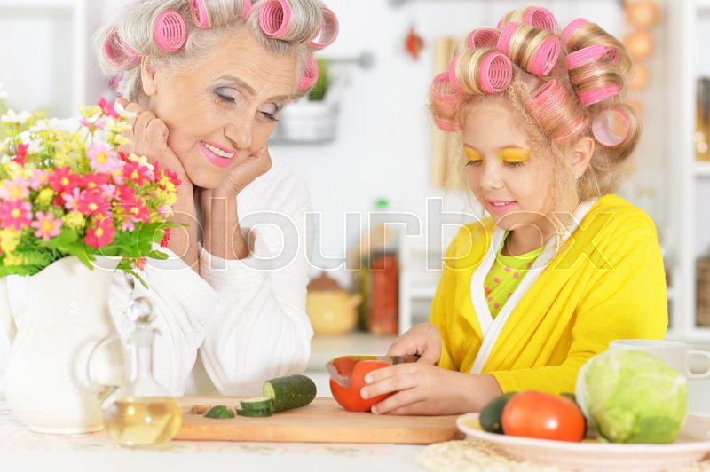 Stock image of 'Senior woman and granddaughter at kitchen with  vegetables'