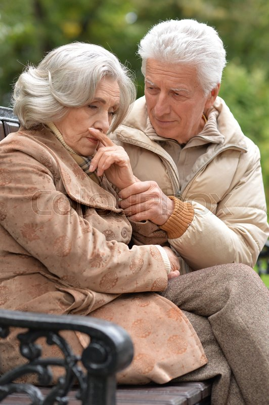 Stock image of 'Portrait of a sad elderly couple sitting on a bench in autumn park'