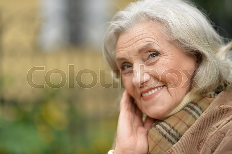 Stock image of 'Portrait of a beautiful middle-aged woman in autumn park'