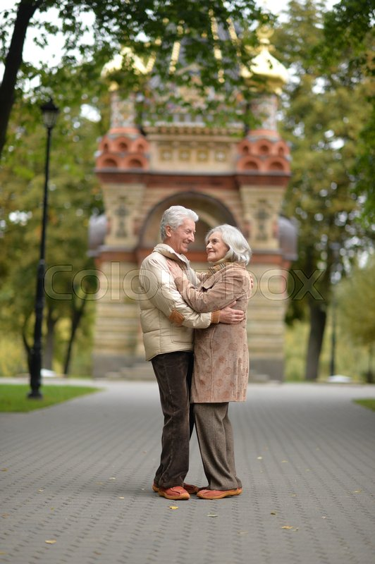 Stock image of 'Beautiful happy elderly couple walking in the autumn park'