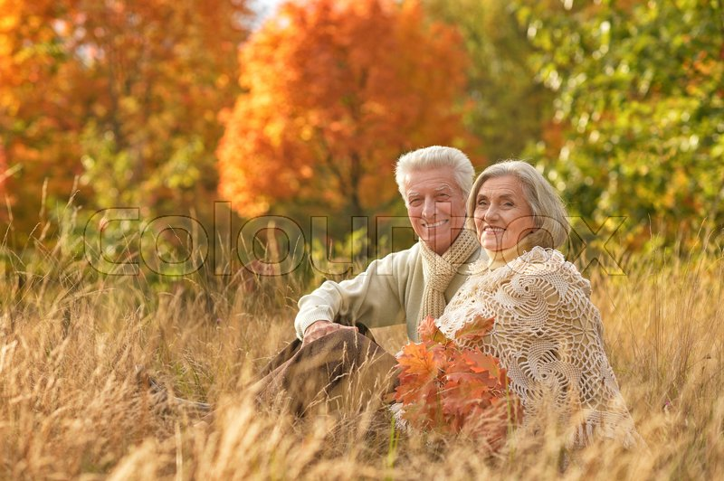 Stock image of 'Portrait of a beautiful happy middle-aged couple in the autumn park'
