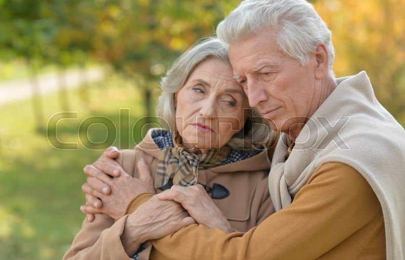 Stock image of 'Portrait of a sad elderly couple standing embracing outdoors'