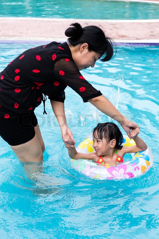 Stock image of 'Asian Chinese Mom Teaching Little Girl Swimming At The Outdoor Pool.'