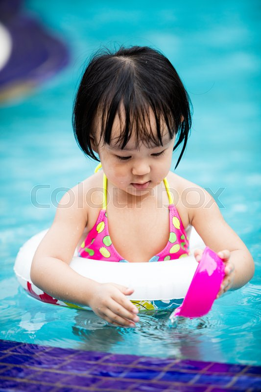 Stock image of 'Asian Chinese Little Girl Playing in the Outdoor Swimming Pool.'
