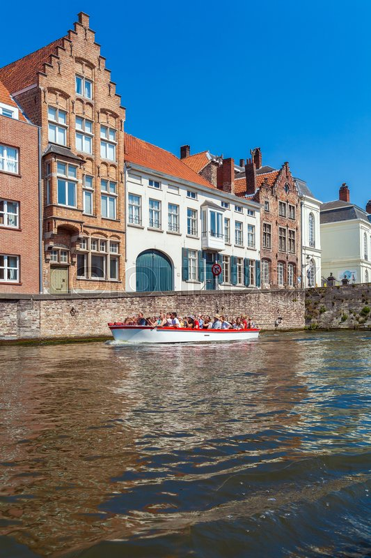 Editorial image of 'BRUGES, BELGIUM - APRIL 6, 2008: Tourists float on a boat through the Dijver channel near vintage homes'