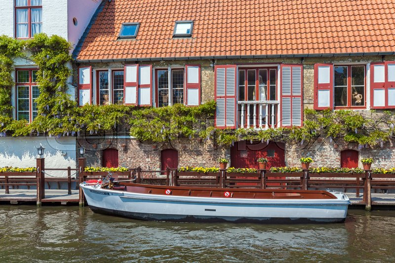 Editorial image of 'BRUGES, BELGIUM - APRIL 6, 2008: Boat on the dock in front of a vintage house channel Dijver'