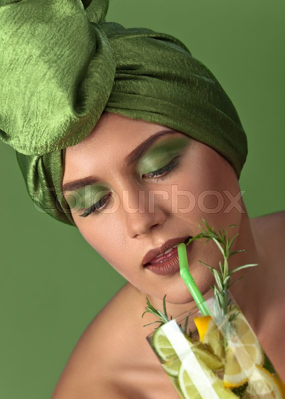 Stock image of 'Young woman with drink from lemon and lime on green background'