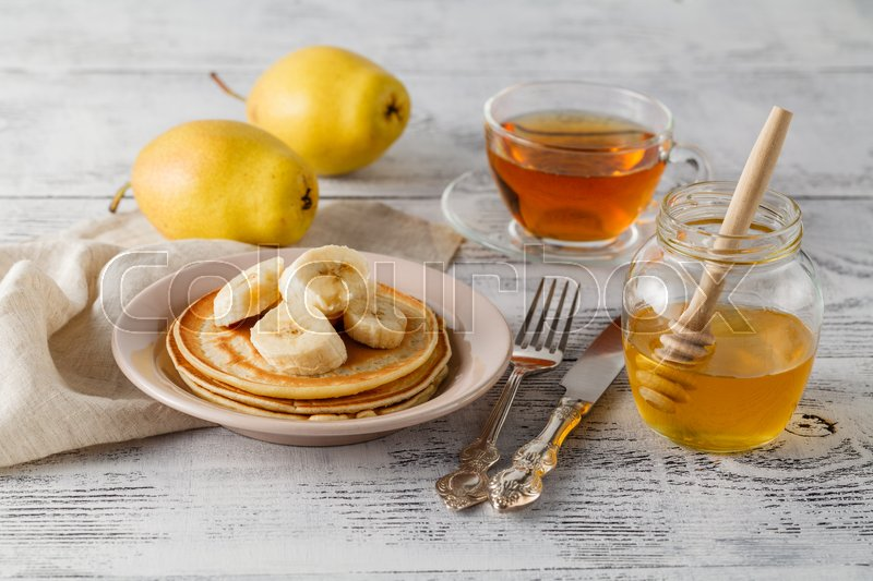 Stock image of 'Stack of pancakes with honey and slices of banana on rustic wooden background'