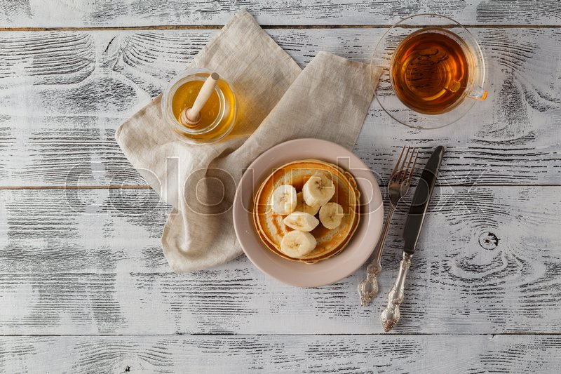 Stock image of 'Pancake with banana, covered with honey or maple syrup with copy space'