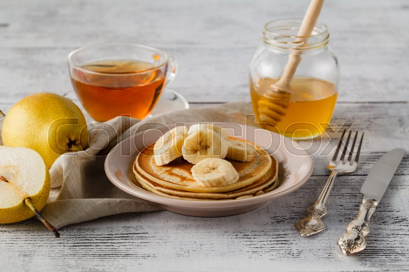 Stock image of 'Stack of pancakes with honey syrup and butter in a white plate on a wooden rustic table'