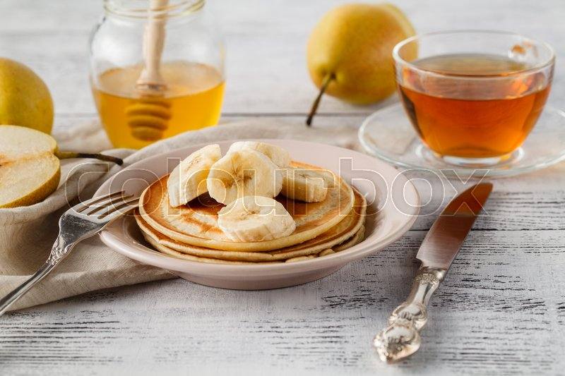 Stock image of 'Closeup delicious and healthy breakfast of pancakes with honey, nuts and caramelized bananas on wooden surface with copy space'