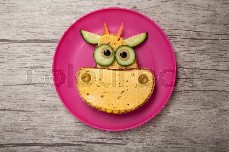 Stock image of 'Cow made of bread and cheese on plate and board'