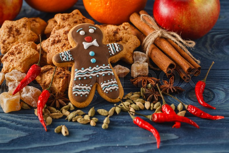 Stock image of 'Gingerbread man with sugar, spices, and vintage rolling pin on rustic, dark wood background. Low key still life with directional, natural lighting for effect.'