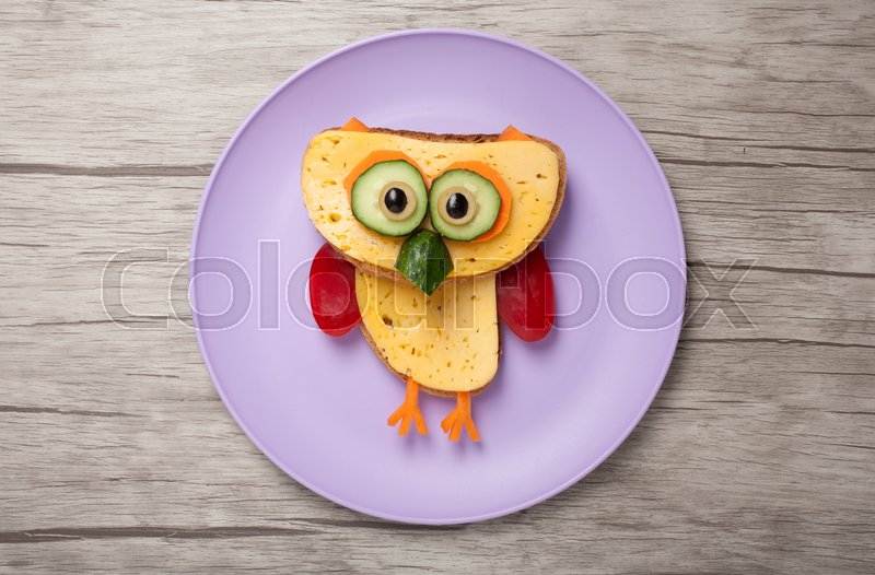 Stock image of 'Owl made of bread, cheese and vegetables on plate and desk'