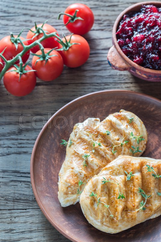 Stock image of 'Grilled chicken with cranberry sauce and fresh cherry tomatoes'