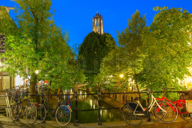 Stock image of 'Dom Tower and bridge with bikes over canal Oudegracht in the night colorful illuminations in the blue hour, Utrecht, Netherlands'