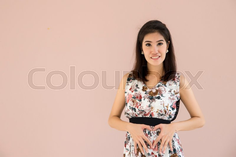 Stock image of 'young pregnant model standing and her belly. Future mom expecting baby. Maternity concept. Copy space for text message'