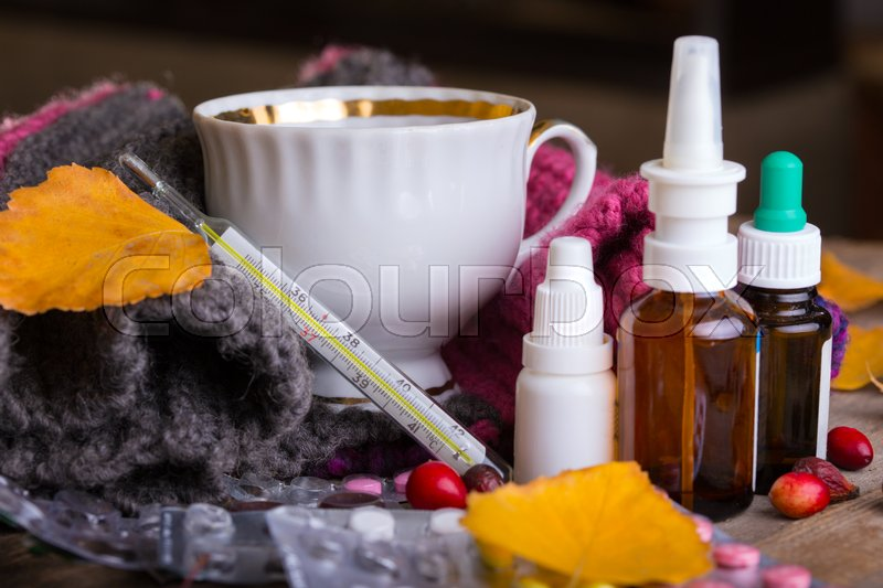Stock image of 'Fall and health care. home pharmacy - cup of tea, pills and thermometer on a wooden background\'