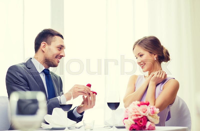 Stock image of 'restaurant, couple and holiday concept - smiling man proposing to his girlfriend at restaurant'