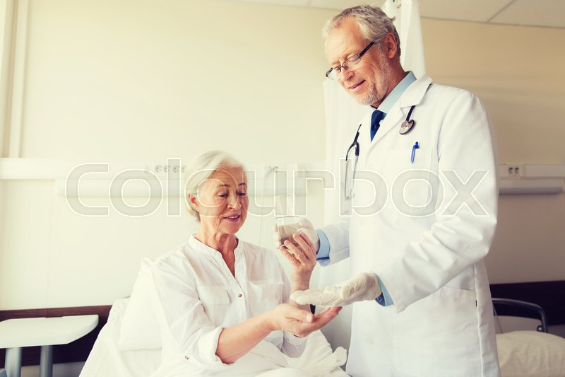 Stock image of 'medicine, age, health care and people concept - doctor giving medication and water to senior woman at hospital ward'