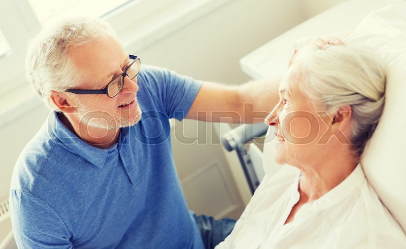 Stock image of 'medicine, age, support, health care and people concept - happy senior man visiting and cheering his woman lying in bed at hospital ward'