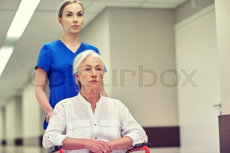 Stock image of 'medicine, age, support, health care and people concept - nurse taking senior woman patient in wheelchair at hospital corridor'
