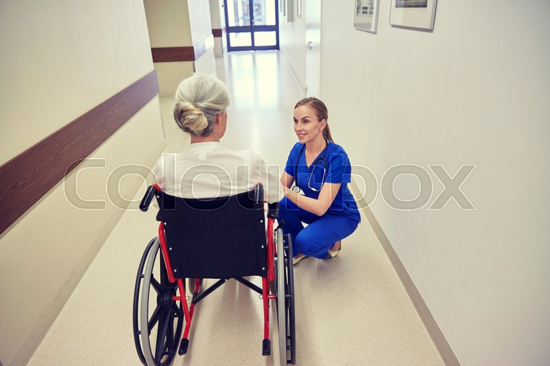 Stock image of 'medicine, age, support, health care and people concept - happy nurse talking to senior woman patient in wheelchair at hospital corridor'