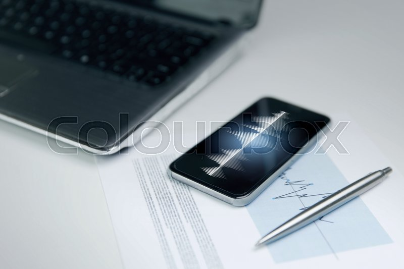 Stock image of 'business, technology and statistics concept - close up of smartphone with sound wave or signal diagram on screen, laptop computer and chart with pen on office table '