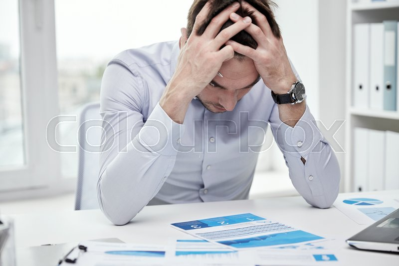 Stock image of 'business, people, paperwork and deadline concept - stressed businessman with papers and charts sitting at table in office'