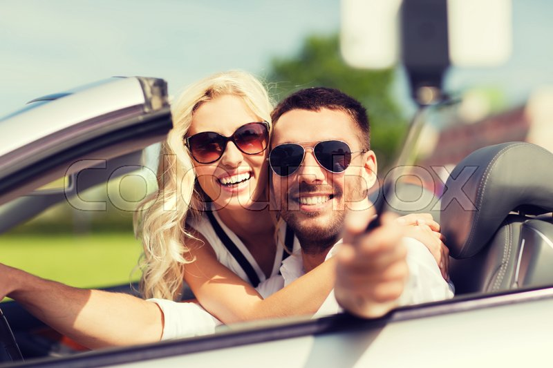 Stock image of 'road trip, leisure, couple, technology and people concept - happy man and woman driving in cabriolet car and taking picture with smartphone on selfie stick'