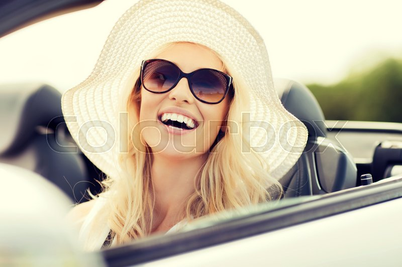 Stock image of 'transport, leisure and people concept - face of happy woman in summer hat and sunglasses driving cabriolet car outdoors'