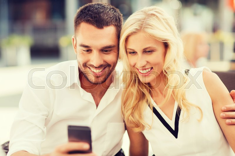 Stock image of 'love, date, technology, people and relations concept - smiling happy couple with smatphone at city street cafe'