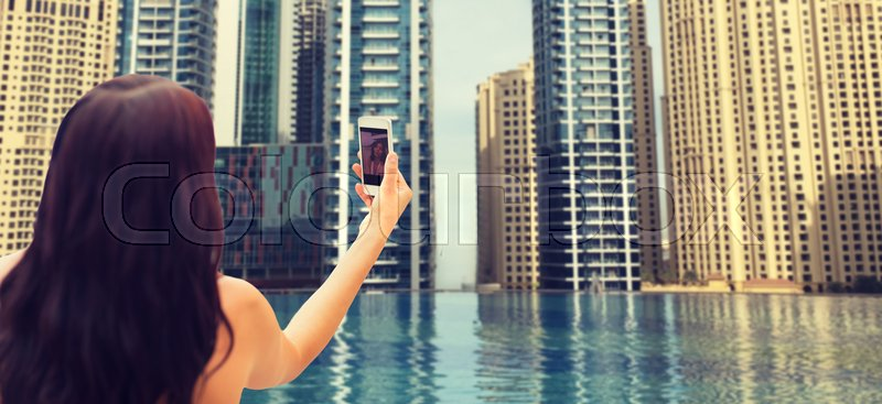 Stock image of 'summer, travel, tourism, technology and people concept - close up of sexy young woman taking selfie with smartphone over infinity edge swimming pool in dubai city background'