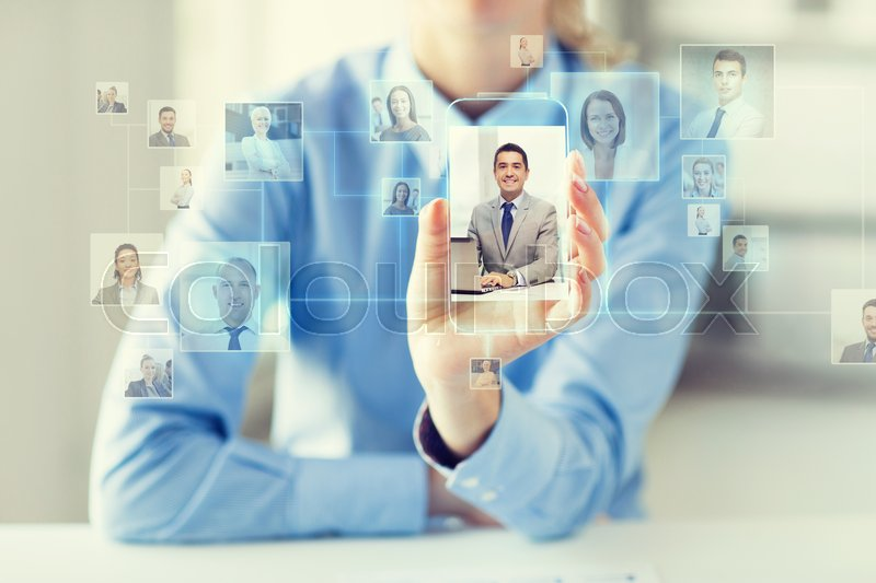 Stock image of 'business, technology, social network, head hunting and people concept - close up of woman hand holding and showing transparent smartphone with contact icons on screen at office'