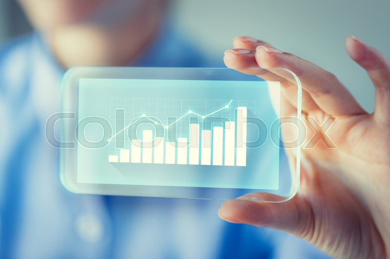 Stock image of 'business, technology, satistics and people concept - close up of woman hand holding and showing transparent smartphone screen with diagram chart'